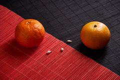 Tangerines in plate on black and red background. Tangerines with slices in plate on black and red background Stock Image