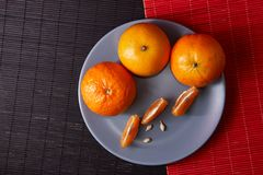 Tangerines in plate on black and red background. Tangerines with slices in plate on black and red background Stock Photos