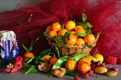 Tangerines. still life. A wicker basket full of mandarin, lit by the light of a candle, Christmas atmosphere Stock Image