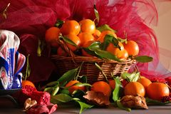 Tangerines. still life. A wicker basket full of mandarin, lit by the light of a candle, Christmas atmosphere Stock Photo