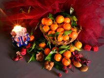 Tangerines. still life. A wicker basket full of mandarin, lit by the light of a candle, Christmas atmosphere Stock Photos