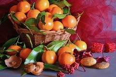 Tangerines. still life. A wicker basket full of mandarin, lit by the light of a candle, Christmas atmosphere Royalty Free Stock Photo