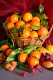 Tangerines. still life. A wicker basket full of mandarin, lit by the light of a candle, Christmas atmosphere Royalty Free Stock Photos