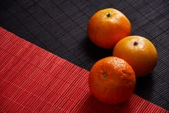 Tangerines mandarins, clementines, citrus fruits on style black and red background with copy space. Tangerines on style black and red background with copy space Royalty Free Stock Image