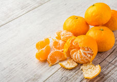 Tangerines on the table. Tangerines, peeled tangerine and tangerine slices on a white wooden table Royalty Free Stock Photo