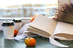 Tangerines and vintage books on a marble table by the window Stock Image