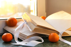 Tangerines and vintage books on a marble table by the window Stock Photos