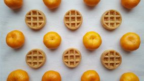 Tangerines and waffles lie on a wooden tray stock photography