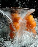 Tangerines and water. Falling on it with waves Stock Image