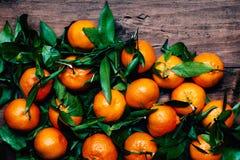 Tangerines z liśćmi na drewnianym tle Mandarynu Tangerine obraz royalty free
