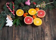 Tangerines z liśćmi w Bożenarodzeniowym wystroju z choinką, suchą pomarańcze i cukierkami nad starym drewnianym stołem, Wieśniaka Zdjęcia Royalty Free
