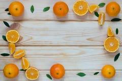 Tangerinescheiben zerlegen an den Rändern der Tabelle Lizenzfreie Stockfotografie