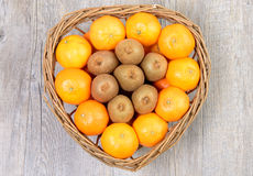 Tangerins and kiwi fruit in basket Stock Photography