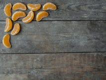 Tangerinskivor på träbakgrund Arkivfoto