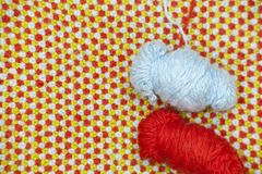 A tangle of blue, woolen yarn on a background of knitted, woolen cloth stock images
