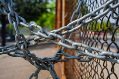 Tangle of Chains On Chainlink Fence, Close Up. A tangle of metal chains hanging off a chainlink fence, close up, web like design Royalty Free Stock Photos