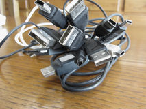 Tangle of dusty computer cables with sockets on the table Stock Photo