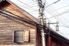Tangle of electrical wires on old wooden house background Royalty Free Stock Photo