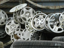 Tangle of hubcaps on a fence. A tangle of vehicle hubcaps hooked on a fence in a junkyard Stock Photography