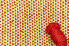 A tangle of red, woolen yarn on a background of knitted, woolen cloth stock photography