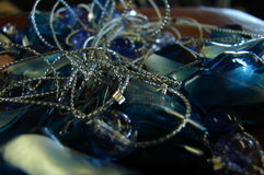 Tangle. A tangle of silver threads and a mixture of blue glass beads Stock Images
