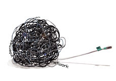 TANGLE Wire Mess. A tagled ball of cables shows a mess in the connection. An ethernet cable plug is shown in the right side of this digital composition Stock Photo
