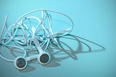 Tangled Ear buds. Backlit in blue with harsh shadowing Royalty Free Stock Photos