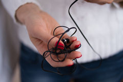 Tangled earphones. Inclusion and listening to music with headphones on your smartphone Royalty Free Stock Image