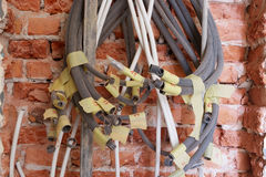 Tangled electrical conduits and cables. Tangled electrical conduits and cables on the brick wall during renovation works royalty free stock image