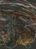 Tangled färgade trådar på svart flöda för bakgrundsregnbågetrådar Arkivbilder