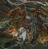 Tangled färgade trådar på svart flöda för bakgrundsregnbågetrådar Arkivfoto
