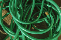 Tangled Green Hose Pipe. A tangled up mess of a used plastic water hose pipe on a concrete patio surface on a sunny morning Stock Images