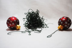 Tangled hooks. A pile of tangled Christmas decoration hooks and two little red and silver baubles Royalty Free Stock Image