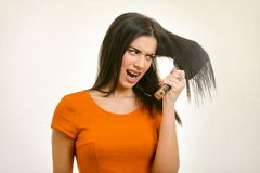 Tangled messy hair stuck on hairbrush. Tangled messy problem hair stuck on hairbrush. Isolated angry young woman royalty free stock images