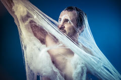 Tangled, naked man trapped in a huge spider web Royalty Free Stock Photo