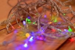 Tangled soft christmas lights over a wooden background. Colorful celebration scene with some blurred lights at the foreground creating a magical lighting image Stock Photography
