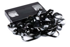 Tangled video tape. VHS video cassette with tangled video tape isolated on white stock photo