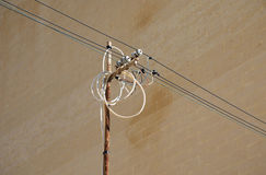 Tangled wires on power pole. Against a wall Royalty Free Stock Image