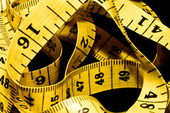 Tangled yellow tape measure. With centimeters and inches stock photos