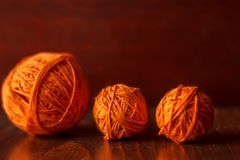 Tangles of orange threads for knitting lie on a wooden table stock photos