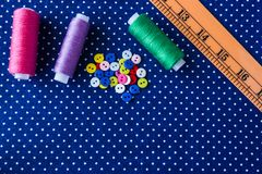 Tangles of threads and colored buttons on the blue fabric. Set for needlework, home sewing royalty free stock images
