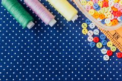 Tangles of threads and colored buttons on the blue fabric. Set for needlework, home sewing stock image