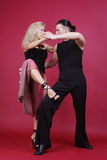 Tango. Beautiful blond and brunet dancing tango on red background Stock Photography