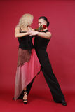 Tango. Beautiful blond and brunet with rose in teeth dancing tango on red background Royalty Free Stock Photos