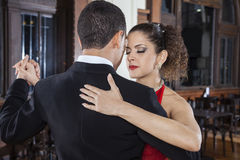 Tango Dancer Closing Eyes While Performing Gentle Embrace With M. Female tango dancer closing eyes while performing gentle embrace step with men in restaurant Royalty Free Stock Image