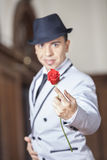 Tango Dancer Holding Fresh Rose While Performing In Restaurant. Portrait of confident male tango dancer holding fresh rose while performing in restaurant Stock Photo