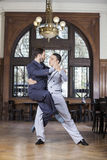 Tango Dancer Lifting Male Partner In Restaurant. Confident tango dancer lifting male partner in restaurant Stock Images