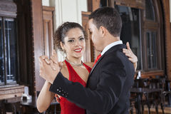 Tango Dancer Performing Gentle Embrace Step With Man. Portrait of female tango dancer performing gentle embrace step with men in restaurant Royalty Free Stock Image