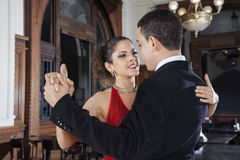 Tango Dancer And Young Man Performing Gentle Embrace. Beautiful female Argentine tango dancer and young men performing gentle embrace in restaurant Stock Photography