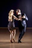 Tango dancers in dance studio. Tango dancers dancing with dramatic lighting in studio Royalty Free Stock Image